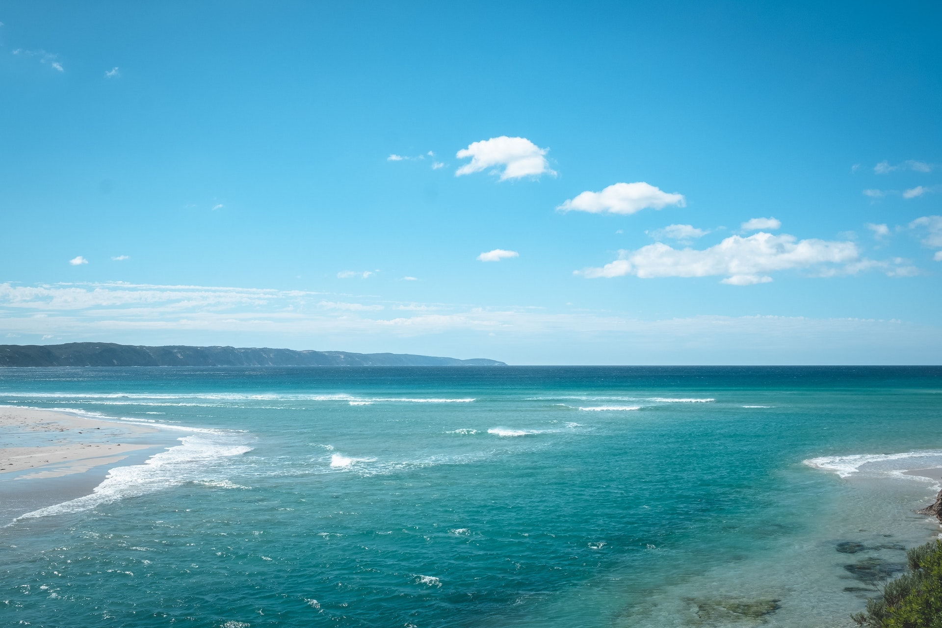 Breathtaking view of vast turquoise sea waving peacefully under cloudless blue sky on sunny day in tropical resort