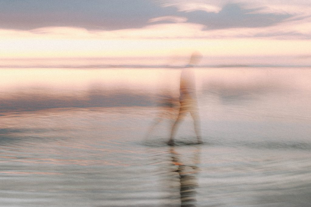 Blurred silhouette of male standing near calm sea against sunset sky in evening time in nature in summer evening outside