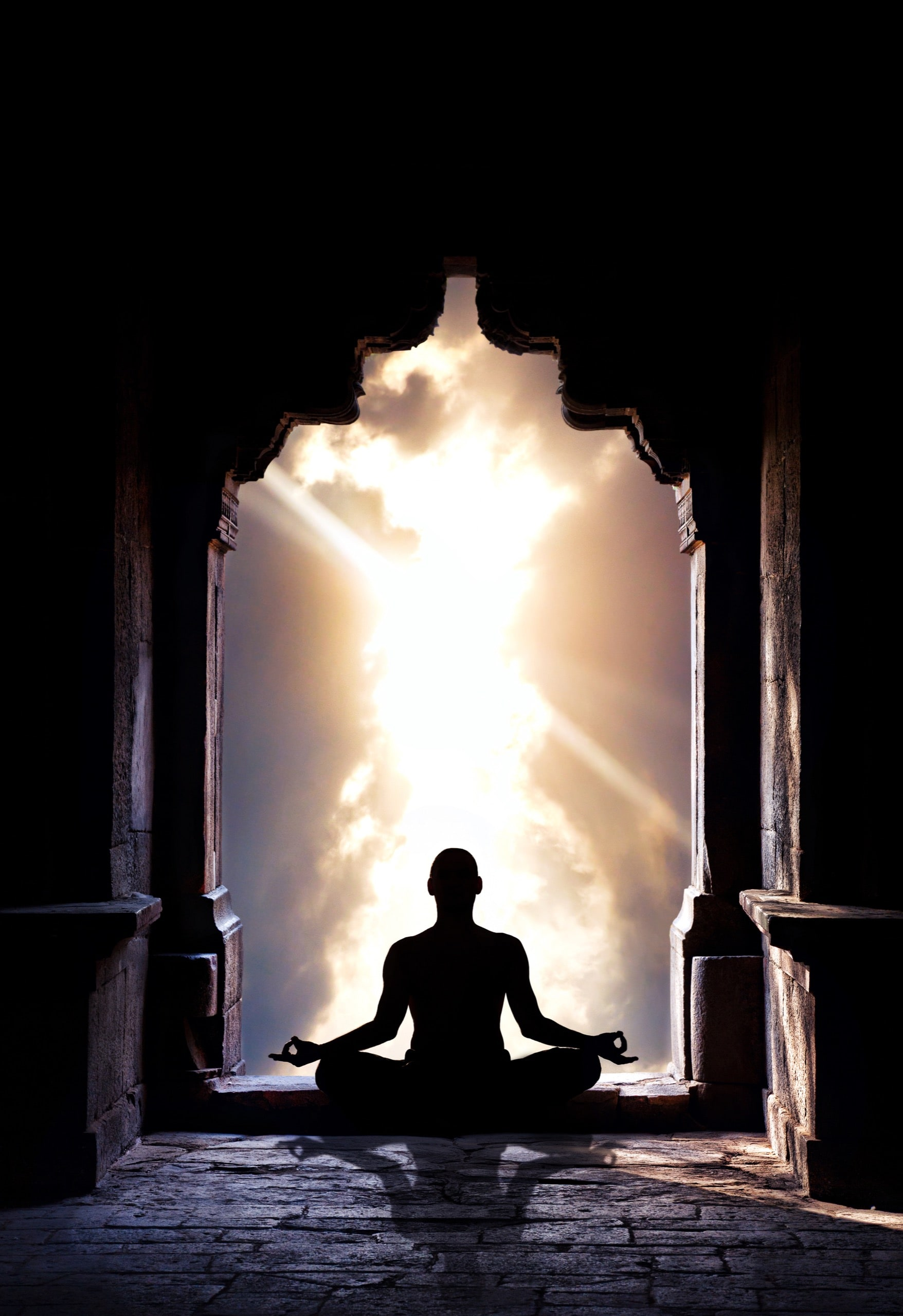 Yoga meditation in lotus pose by man silhouette in old temple arch at dramatic sky background. Free space for text