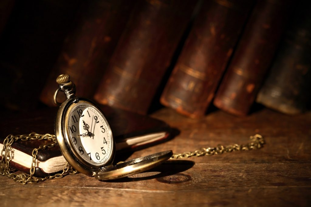 Vintage pocket watch on wooden surface against old books
