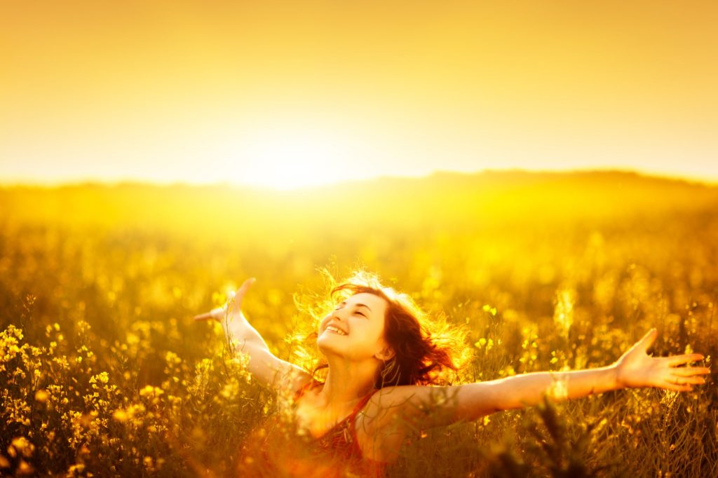 Young happy woman in canola field on sunset.