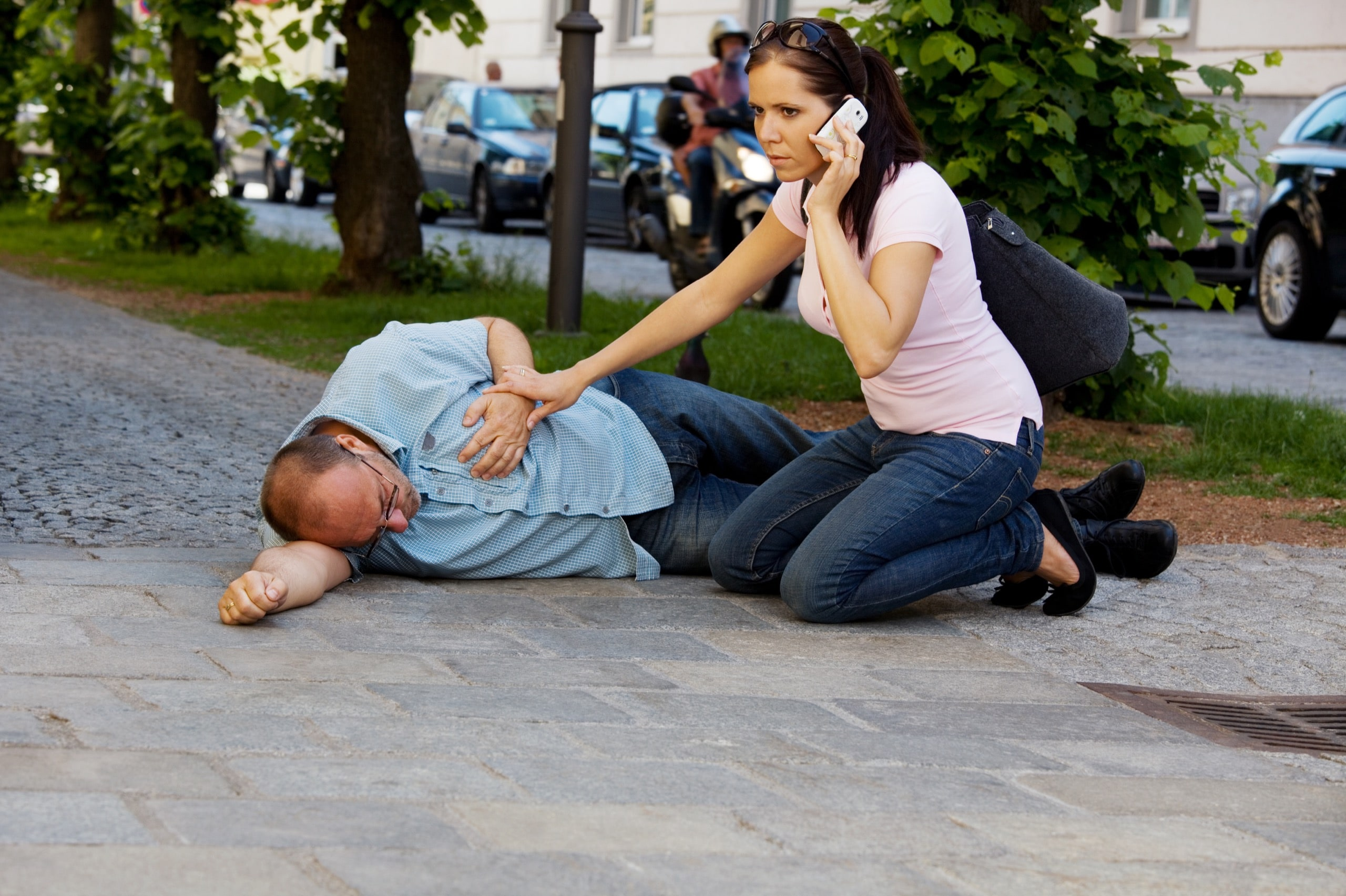 A man has a dizzy spell or a heart attack. Woman comes to the rescue.